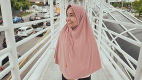 La muchacha sonriente en hijab va detrás de la cámara en la transición sobre tráfico por carretera jakarta indonesia almacen de video