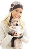 La muchacha sonriente en invierno viste con una taza blanca de bebida caliente Imagenes de archivo