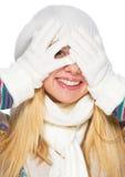 La muchacha sonriente en invierno viste la mirada hacia fuera de las manos Fotos de archivo libres de regalías
