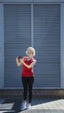 La muchacha sonriente en la camisa roja que tomaba una foto en smartphone, contra el metal rayó el fondo Día, al aire libre Foto de archivo libre de regalías