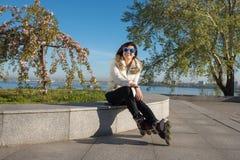 La muchacha sonriente en las gafas de sol divertidas descansa después de patinaje sobre ruedas Fotografía de archivo