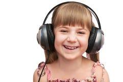 La muchacha sonriente en los auriculares Imagen de archivo libre de regalías