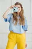La muchacha sonriente en paño casual hace la foto por la cámara portante Foto de archivo