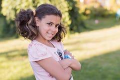 la muchacha sonriente en pantalones cortos está en el jardín Imagen de archivo libre de regalías