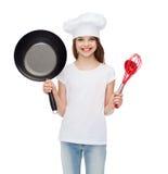 La muchacha sonriente en sombrero del cocinero con la cucharón, bate y critica Fotografía de archivo