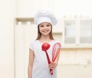 La muchacha sonriente en sombrero del cocinero con la cucharón y bate Imagen de archivo