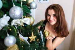 La muchacha sonriente en un vestido negro adorna el árbol de navidad Imagen de archivo