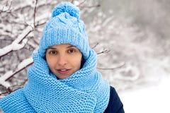La muchacha sonriente en una bufanda azul hecha punto, y casquillo se coloca Fotos de archivo libres de regalías