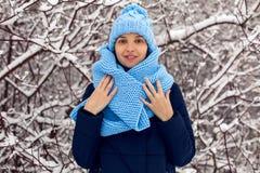 La muchacha sonriente en una bufanda azul hecha punto, y casquillo se coloca Imágenes de archivo libres de regalías