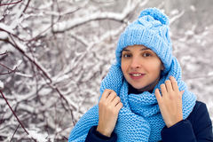 La muchacha sonriente en una bufanda azul hecha punto, y casquillo se coloca Imagen de archivo