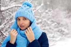 La muchacha sonriente en una bufanda azul hecha punto, y casquillo se coloca Imagenes de archivo