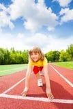 La muchacha sonriente en uniforme alista para funcionar con maratón Foto de archivo
