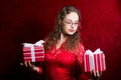 La muchacha sonriente en vidrios con dos rayó la caja de regalo Imagen de archivo libre de regalías