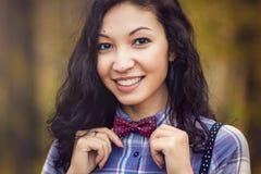 La muchacha sonriente endereza la corbata de lazo Fotografía de archivo libre de regalías