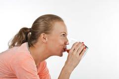 La muchacha sonriente está bebiendo el jugo de tomate. Foto de archivo libre de regalías