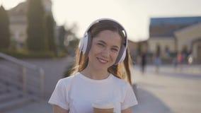 La muchacha sonriente está escuchando la música en auriculares más grandes 4K almacen de video