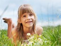 La muchacha sonriente está mintiendo en el prado Foto de archivo