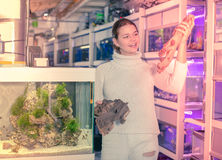 La muchacha sonriente está sosteniendo la piedra arenisca amarillo-marrón grande para el aquariu Foto de archivo libre de regalías