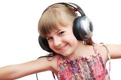 La muchacha sonriente está sosteniendo los auriculares Imagen de archivo