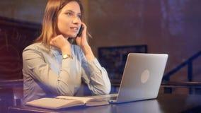 La muchacha sonriente, freelancer que habla en el teléfono, trabajando tarde Retrato resbalador 4K almacen de video