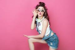 La muchacha sonriente fresca de la moda bonita con los auriculares hizo punto las gafas de sol del bolso llevando la ropa colorid Fotos de archivo libres de regalías