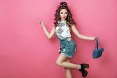 La muchacha sonriente fresca de la moda bonita con los auriculares hizo punto las gafas de sol del bolso llevando la ropa colorid Foto de archivo