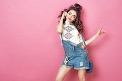 La muchacha sonriente fresca de la moda bonita con los auriculares hizo punto llevar del bolso ropa colorida con la música que es Fotografía de archivo