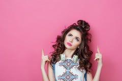 La muchacha sonriente fresca de la moda bonita con los auriculares que llevan la ropa colorida con el pelo rizado mira en el asom Imagen de archivo
