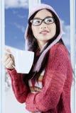 La muchacha sonriente goza de la bebida caliente Fotos de archivo libres de regalías
