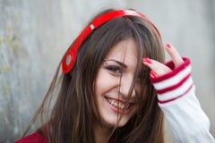 La muchacha sonriente hermosa del adolescente con la perforación y compone música que escucha en auriculares Foco selectivo Imagen de archivo libre de regalías