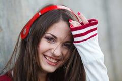 La muchacha sonriente hermosa del adolescente con la perforación y compone música que escucha en auriculares Foco selectivo Foto de archivo