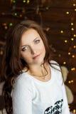 La muchacha sonriente hermosa en chaqueta blanca caliente se sienta cerca de la ventana al lado de la pared en las luces Foto de archivo libre de regalías
