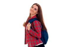 La muchacha sonriente hermosa en una camisa de tela escocesa con una mochila en su parte posterior es Fotografía de archivo