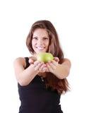 La muchacha sonriente hermosa estira la manzana verde Fotografía de archivo libre de regalías