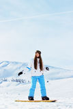 La muchacha sonriente hermosa joven de la snowboard con googlea en su montar a caballo principal en snowboard en las montañas nev Imagenes de archivo