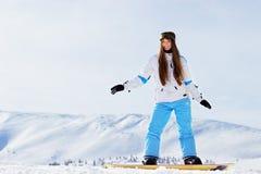 La muchacha sonriente hermosa joven de la snowboard con googlea en su montar a caballo principal en snowboard en las montañas nev fotografía de archivo libre de regalías