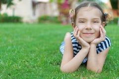 La muchacha sonriente hermosa miente en hierba verde Foto de archivo libre de regalías