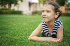 La muchacha sonriente hermosa miente en hierba verde Imágenes de archivo libres de regalías