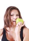 La muchacha sonriente hermosa muerde la manzana verde fresca Foto de archivo libre de regalías