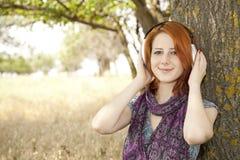 La muchacha sonriente joven con los auriculares acerca al árbol. Fotografía de archivo