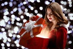 La muchacha sonriente joven en un traje virginal de la nieve s abre un regalo por el Año Nuevo 2018,2019 Imagen de archivo libre de regalías