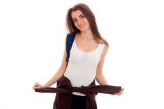 La muchacha sonriente joven en una camiseta blanca se levanta recta y mantiene la chaqueta de las manos aislada en el fondo blanc Fotos de archivo