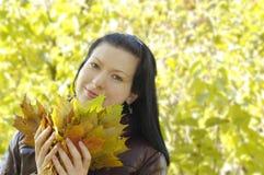 La muchacha sonriente joven sostiene las hojas de otoño Fotos de archivo