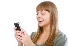 La muchacha sonriente lee el mensaje en el teléfono Foto de archivo