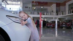 La muchacha sonriente linda del niño abraza el faro del coche en salón auto almacen de video