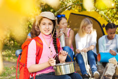 La muchacha sonriente lleva el sombrero, pote metálico de los controles en el campo Imágenes de archivo libres de regalías