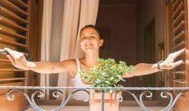 La muchacha sonriente mira fuera de la ventana Imagen de archivo