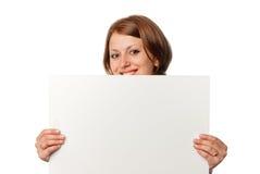 La muchacha sonriente mira hacia fuera de la hoja en blanco Imagenes de archivo