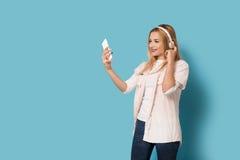La muchacha sonriente mira su smartphone Foto de archivo libre de regalías