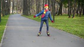 La muchacha sonriente monta en parque del otoño en rollerblades almacen de metraje de vídeo
